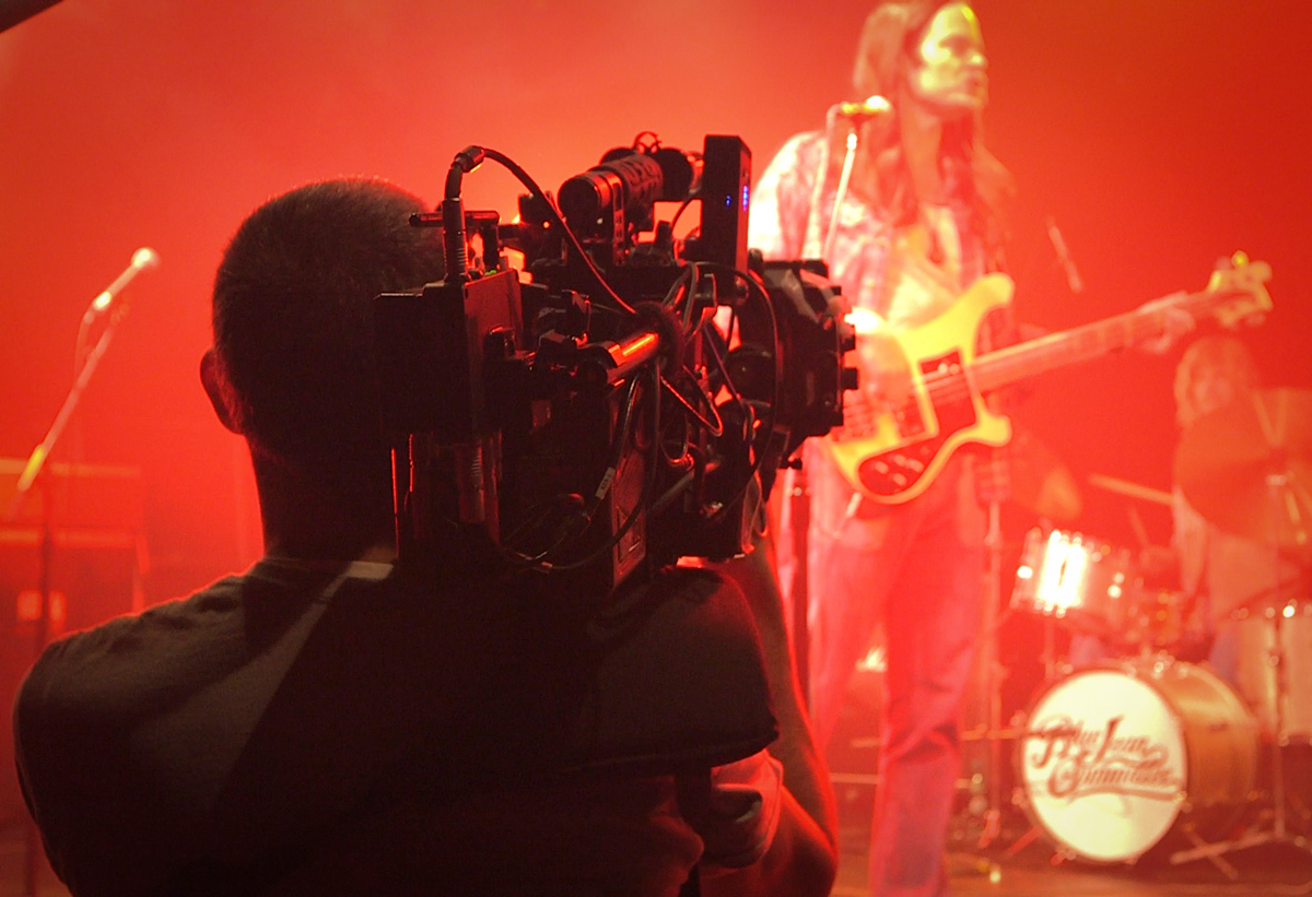 """Operator Chris Cuevas shoots Bill Hader during a faux """"Blue Jean Committee"""" concert. Director of Photography/Co-Director Alex Buono purposely highlighted red stage lighting, commonplace in the period Eagles concerts parodied in the episode / Photo Courtesy of Rhys Thomas"""